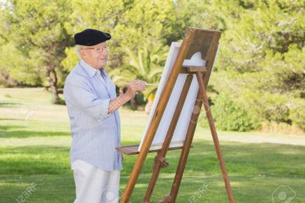 Old man wearing a beret painting in the park using an easel
